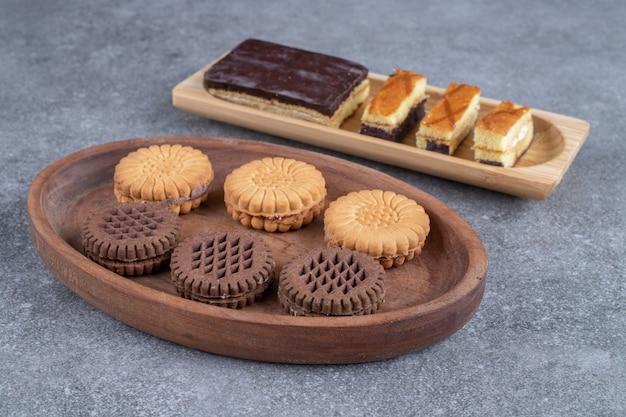 Pęczek pysznych herbatników i kawałków ciasta na drewnianych talerzach