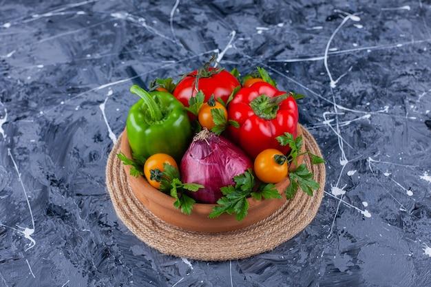 Pęczek pysznych zdrowych świeżych warzyw w glinianej misce.