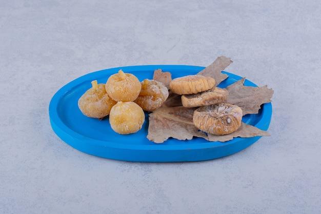 Pęczek słodkich suszonych fig ułożonych na niebieskim talerzu.