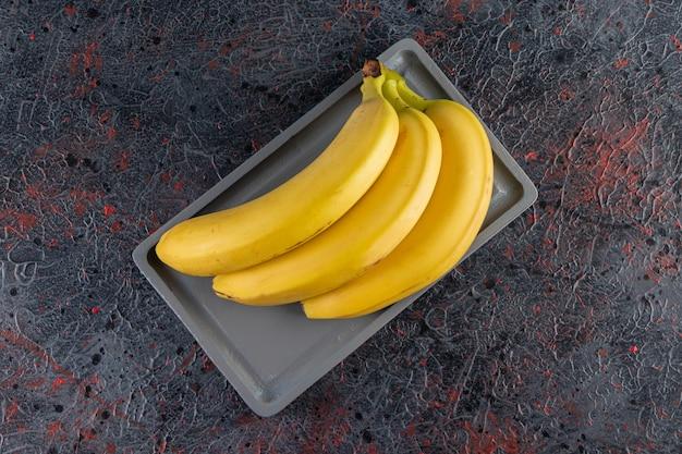 Pęczek soczystego żółtego banana ułożony na ciemnym talerzu.