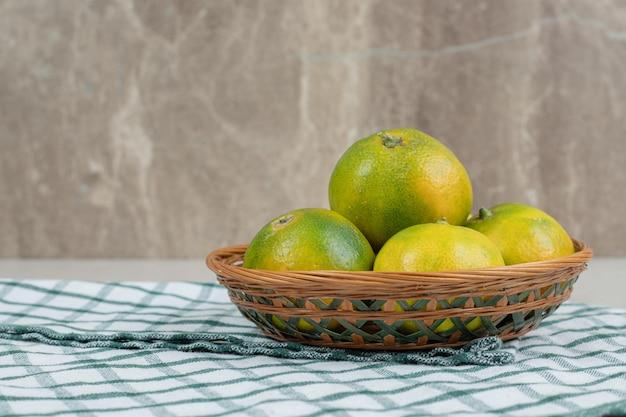 Pęczek soczystych mandarynek w drewnianym koszu.