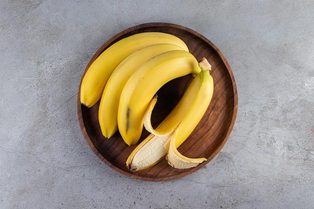 Pęczek soczystych żółtych bananów ułożonych na kamiennym stole.