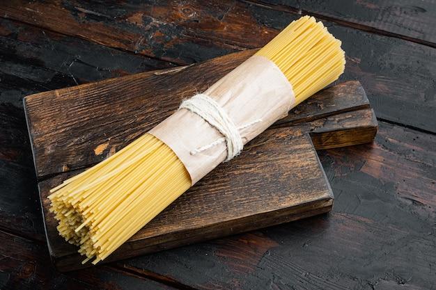 Pęczek spaghetti, zestaw surowego włoskiego makaronu, na drewnianej desce do krojenia, na starym ciemnym drewnianym stole