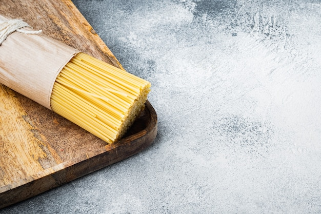 Pęczek spaghetti, zestaw surowego włoskiego makaronu, na drewnianej tacy, na szaro