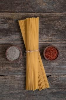 Pęczek suchego, niegotowanego spaghetti i przypraw ułożonych na drewnianej powierzchni. wysokiej jakości zdjęcie