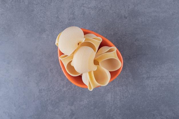 Pęczek surowego makaronu muszli w misce pomarańczy.