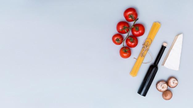 Pęczek surowego makaronu spaghetti; pomidor; grzyb; butelka sera i oleju do robienia smacznego makaronu