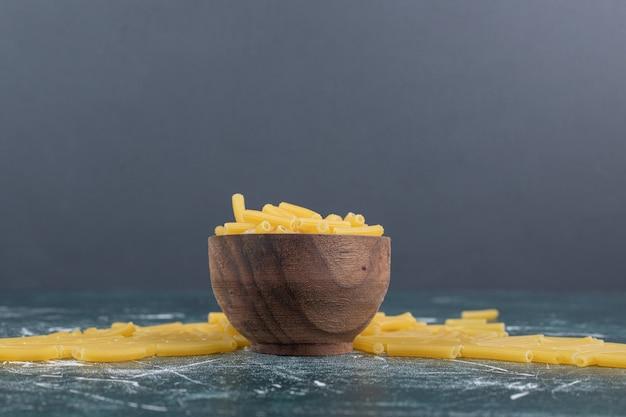 Pęczek surowego makaronu w drewnianej misce. wysokiej jakości zdjęcie