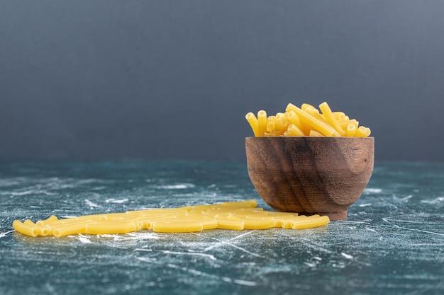 Pęczek surowego makaronu w drewnianej misce.