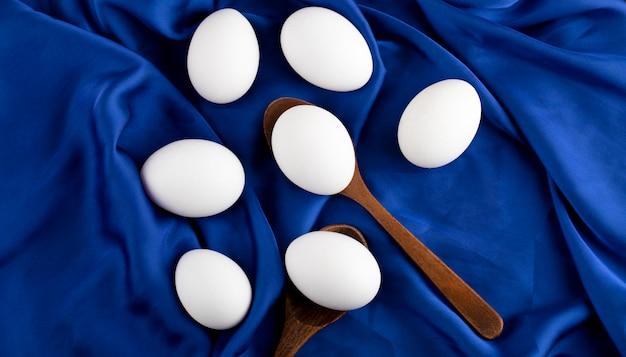 Pęczek surowych jaj z drewnianą łyżką na niebieskim satynowym szmatce.
