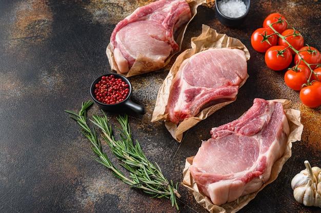 Pęczek surowych kotletów wieprzowych ułożonych z ziołami, olejem i przyprawami. gotowanie mięsa. na ciemnym tle z miejscem na tekst