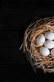 Pęczek surowych świeżych jaj w ptasie gniazdo na czarnej powierzchni. wysokiej jakości zdjęcie
