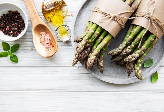 Pęczek surowych szparagów łodyg z różnymi przyprawami i składnikami na podłoże drewniane