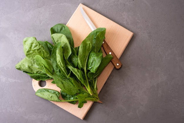 Pęczek świeżego szpinaku na desce do krojenia z nożem na szarym tle, zdrowa, surowa dieta, z bliska.