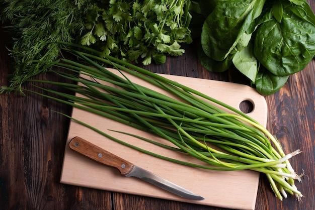 Pęczek świeżej zielonej cebuli z zielenią na desce do krojenia na drewnianym tle, styl rustykalny, przydatne wegetariańskie jedzenie koncepcja, z bliska.