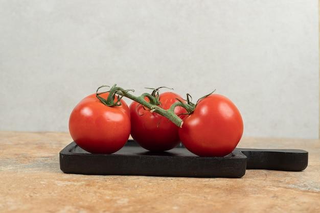 Pęczek świeżych, czerwonych pomidorów z zielonymi łodygami na ciemnym talerzu