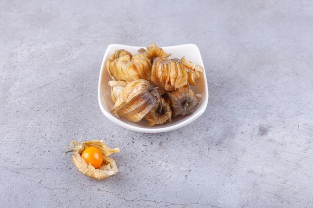 Pęczek świeżych dojrzałych kumkwatów umieszczonych na białym talerzu.