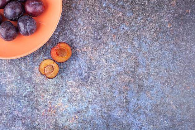 Pęczek świeżych, fioletowych śliwek ułożonych na pomarańczowym talerzu.