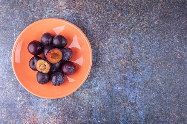 Pęczek świeżych fioletowych śliwek ułożonych na pomarańczowym talerzu.