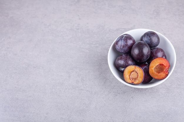 Pęczek świeżych, fioletowych śliwek umieszczonych w białej misce.