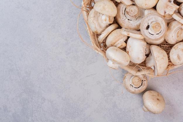 Pęczek świeżych grzybów w drewnianym koszu.