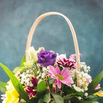 Pęczek świeżych kwiatów umieszczony w wiklinowym koszu