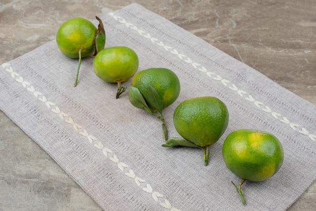 Pęczek świeżych mandarynek na szarym obrusie.