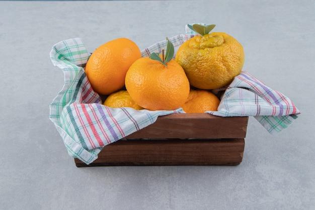 Pęczek świeżych mandarynek w drewnianym pudełku