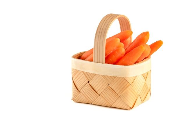 Pęczek świeżych surowych marchewek w wiklinowym koszu na białym tle