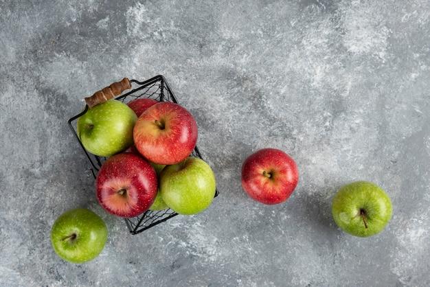Pęczek świeżych zielonych i czerwonych jabłek umieszczonych w metalowym koszu.