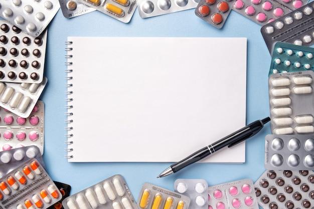Pęczek tabletek w blistrach na niebieskim tle z notatnikiem i piórem, kopia przestrzeń. pusta recepta na receptę leku.