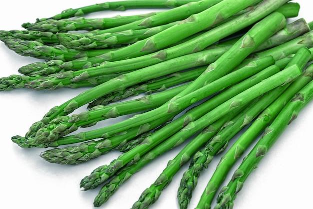 Pęczek włóczni świeżych zielonych szparagów na białym tle na białym stole.