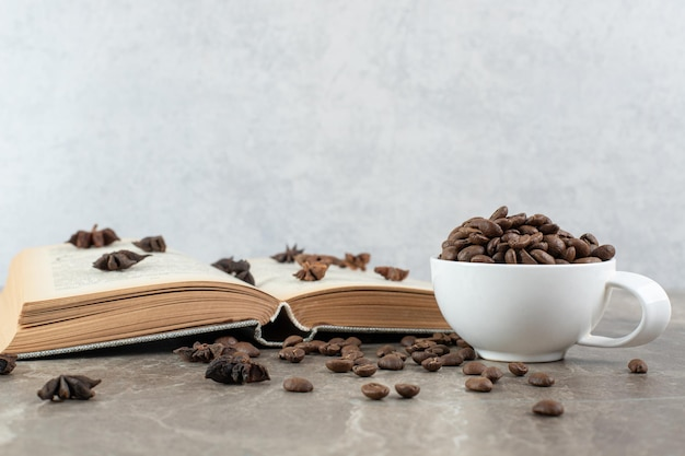 Pęczek ziaren kawy rozrzuconych na książce z filiżanką ziaren.
