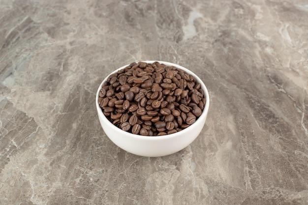 Pęczek ziaren kawy w białej misce