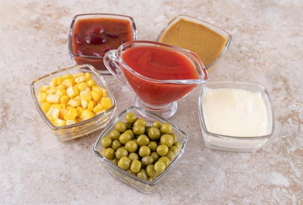 Pęczek zielonego groszku, ziaren kukurydzy, ketchupu, majonezu, musztardy i czerwonego sosu na marmurowej powierzchni.