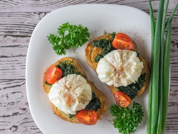 Pęczek zielonej cebuli i jajka w koszulce ze smażonym chlebem na białym talerzu