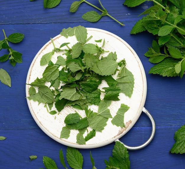 Pęczek zielonej mięty na niebieskim drewnianym tle, pachnąca przyprawa do koktajli i deserów, widok z góry