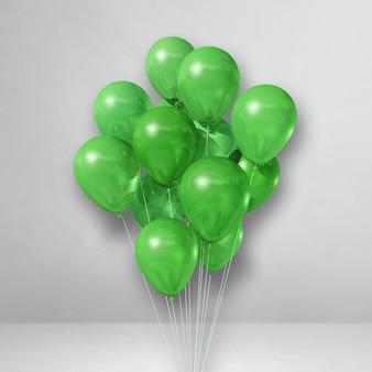 Pęczek zielonych balonów na białej powierzchni