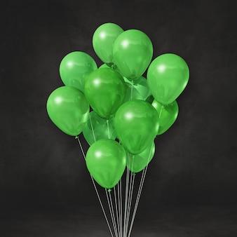 Pęczek zielonych balonów na czarnej ścianie