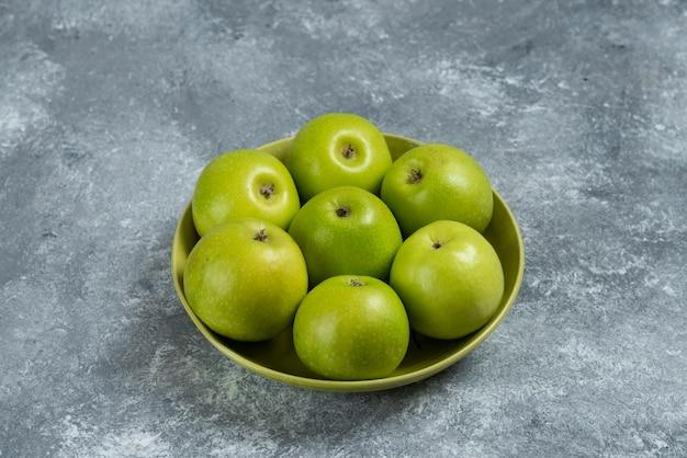 Pęczek zielonych jabłek w zielonej misce.