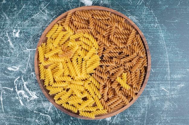 Pęczek żółtego i brązowego makaronu fusilli na drewnianym talerzu. wysokiej jakości zdjęcie