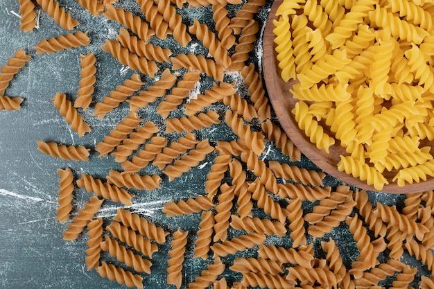 Pęczek żółtego i brązowego makaronu fusilli na niebieskim tle. wysokiej jakości zdjęcie