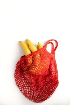 Pęczek żółtych bananów w czerwonej bawełnianej torbie na sznurku na białym. zero marnowania. koncepcja ochrony przyrody na planecie