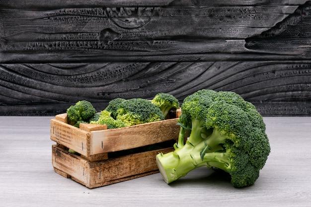 Pęczki brokułów w drewnianym pudełku w pobliżu całego świeżego brokułu