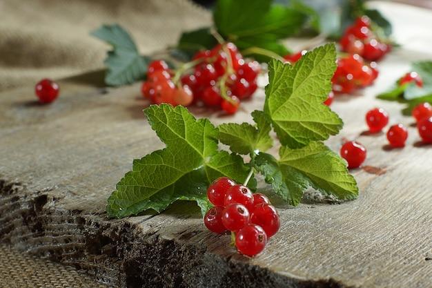 Pęczki czerwonych porzeczek z liśćmi leżą na desce.