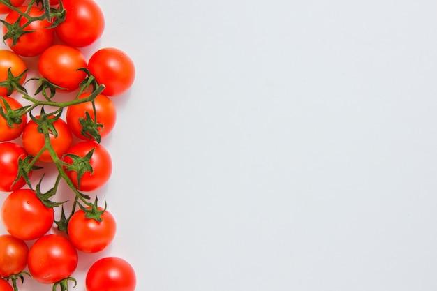 Pęczki pomidorów na białej powierzchni. widok z góry. miejsce na tekst