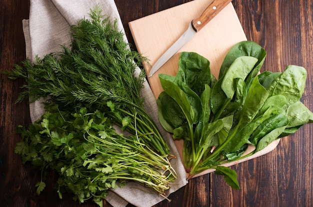 Pęczki świeżo zebranych zieleni szpinaku, koperku, kolendry na tekstyliach i deska do krojenia na ciemnym tle drewnianych, zdrowa żywność, styl rustykalny, z bliska.