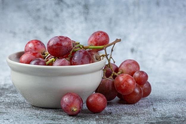 Pęczki świeżych dojrzałych czerwonych winogron na ciemnej powierzchni.