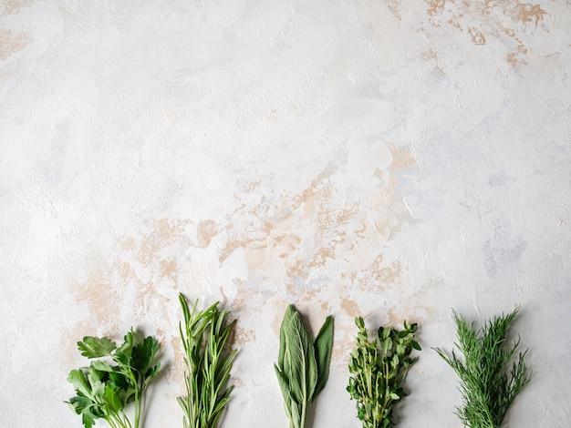 Pęczki świeżych surowych ziół - rozmaryn, tymianek, koperek, pietruszka i szałwia na teksturowanym tle. widok z góry.