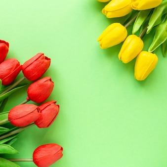 Pęczki żółtych i czerwonych tulipanów na zielonym tle. skopiuj miejsce